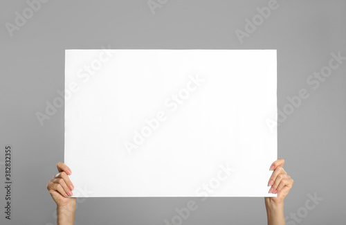 Woman holding white blank poster on grey background, closeup. Mockup for design