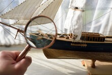 Retro Copper Colored Magnifying Glass (hand Lens) And Wooden Tall Ship Scale Model Close-up. Vintage Still Life. Sailing, Travel, Navigation. Collecting, Souvenir, Optics