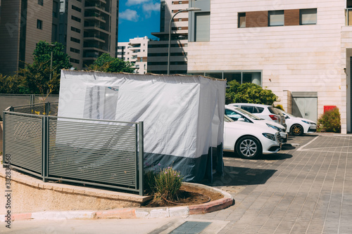 Valokuvatapetti One white blue Sukkah outside on the street with cars near buildings, a traditional building for the Jewish holiday of Sukkot