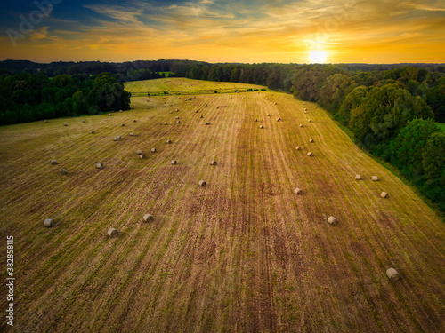 Fototapeta An aerial view of a freshly baled field with a beautiful sunset in the background. obraz