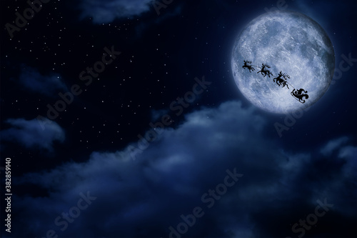 Magic Christmas eve. Santa with reindeers flying in sky on full moon night