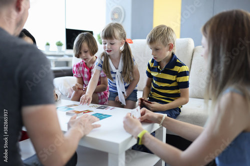 Obraz na plátně Team of three children and team of three adults play board games at home