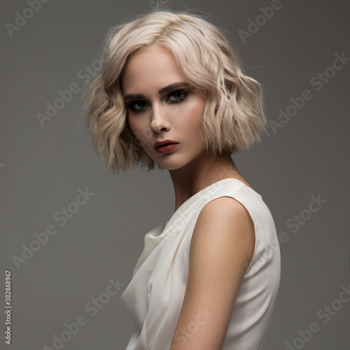 Portrait of attractive blonde woman with curly short hair
