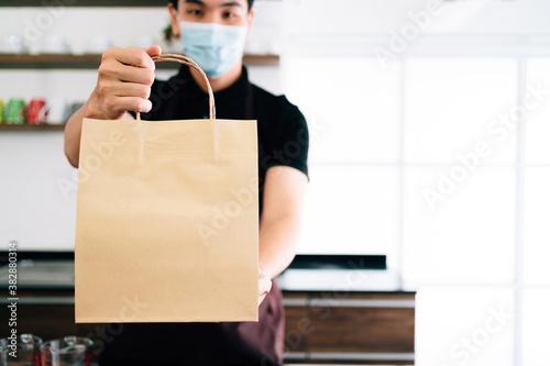 Male barista showing takeaway coffee in the paper bag during Coronavirus outbreak time Fotobehang