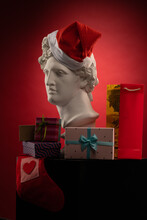 Statue Of Apollo Belvedere In A Red Cap Of Santa Claus, Gifts Boxes And Packages, In Blue Contour Light On Multi-colored Backgrounds. Composition For Congratulations.