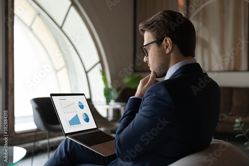 Side back view focused skilled young 30s male marketing specialist in suit analyzing graphs and charts in electronic research report on computer, developing sales growth strategy alone in office Fototapet