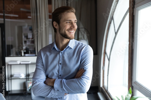 Fototapeta Happy young handsome leader businessman standing with folded hands, looking in distance in window, satisfied with career or thinking of new challenges and professional growth opportunities in office. obraz