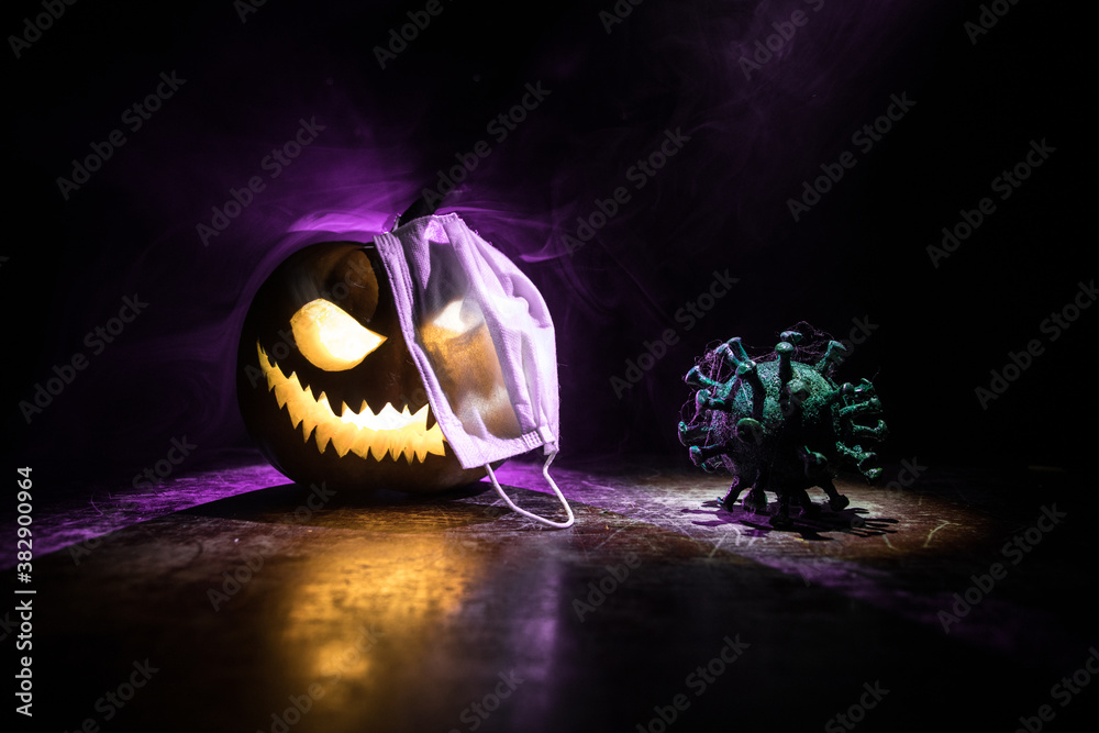 Halloween during Corona virus global pandemic concept. Glowing pumpkins and Covid novel on dark with thematic spooky decorations. Halloween pumpkin on foggy backlight.