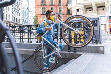 Latino Young Man Carrying Bike...