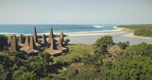 Aerial View Of Traditional Village With Ornately Houses Roof On Sand Beach Sea Shore With Tropic Trees And Plants. Green Grass Valley At Sandy Ocean Coast Sumba Island, Indonesia, Asia At Drone Shot