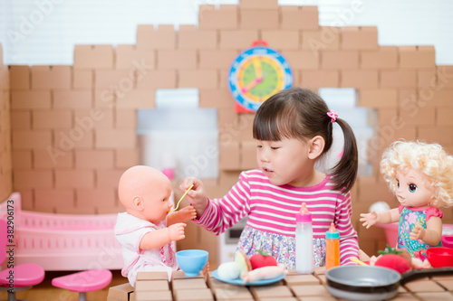 Fototapeta young  girl pretend play babysitting with baby doll at home