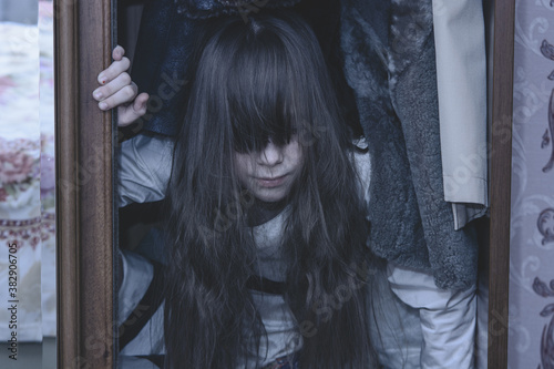 Photo Mad scary girl in cupboard at dark night