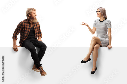 Fototapeta Bearded guy sitting on a white panel and listening to a young woman talking