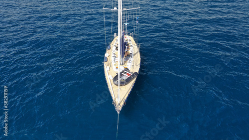 Aerial drone photo of beautiful sailboat anchored in Aegean deep blue sea Fototapete