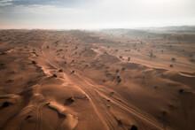 Aerial View Of Car Tracks On The Sand Dunes Of Arabian Desert In Dubai, UAE