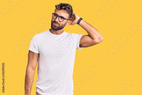 Fototapeta Young hispanic man wearing casual clothes and glasses confuse and wondering about question. uncertain with doubt, thinking with hand on head. pensive concept. obraz