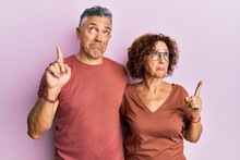 Beautiful Middle Age Couple Together Wearing Casual Clothes Pointing Up Looking Sad And Upset, Indicating Direction With Fingers, Unhappy And Depressed.