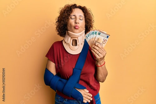 Fotografie, Obraz Beautiful middle age mature woman wearing cervical collar and sling holding insurance euros looking at the camera blowing a kiss being lovely and sexy