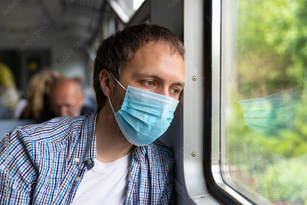 Fototapeta Sad man looking at window, wear face protective mask in train to protect the respiratory system from coronavirus infection, covid-19. Preventive measure. New normal, pandemic concept.