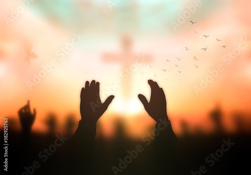 Resurrection of Easter Sunday concept: Silhouette christian people hand rising over blurred cross on spiritual light background