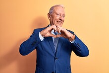 Senior Handsome Grey-haired Businessman Wearing Elegant Suit Over Yellow Background Smiling In Love Doing Heart Symbol Shape With Hands. Romantic Concept.