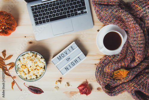 Fototapeta Top view Movie night concept. Flat lay composition with Movie night message on the board, laptop, popcorn bowl, decorative pumpkin, fallen leaves, a cup of tea, and warm plaid on wooden background. obraz
