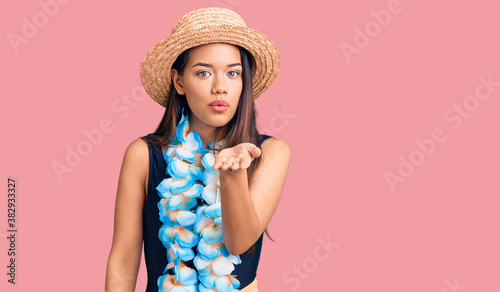 Fototapeta Young beautiful latin girl wearing hawaiian lei and summer hat looking at the camera blowing a kiss with hand on air being lovely and sexy