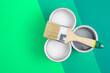 Leinwandbild Motiv Open paint enamel cans on color palette samples. The concept of repair, construction. Shades of green.
