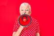 Leinwandbild Motiv Senior beautiful grey-haired woman screaming using megaphone over isolated red background