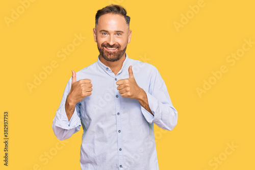 Handsome middle age man wearing business shirt success sign doing positive gesture with hand, thumbs up smiling and happy. cheerful expression and winner gesture.