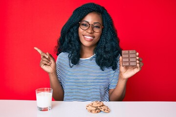 Beautiful african woman eating a chocolate bar and drinking glass of milk smiling happy pointing with hand and finger to the side