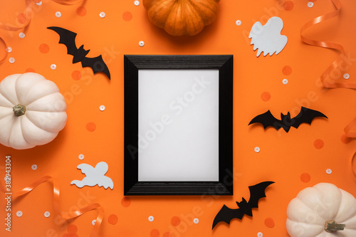 Fototapeta Creative halloween flat lay composition: black frame, bats, pumpkins, confetti and ghost on orange background with place for text, top view