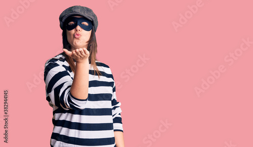 Fotografie, Obraz Young beautiful brunette woman wearing burglar mask looking at the camera blowing a kiss with hand on air being lovely and sexy
