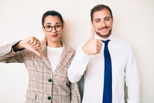 Beautiful Couple Wearing Business Clothes Doing Thumbs Up And Down, Disagreement And Agreement Expression. Crazy Conflict
