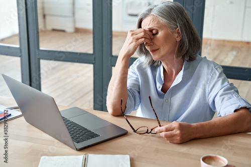 Photo Overworked tired older lady holding glasses feeling headache, having eyesight problem after computer work