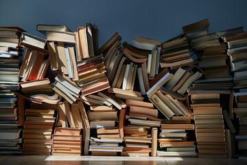 Fototapeta Boks Pile of old books in dramatic dim light sunlight rays through window