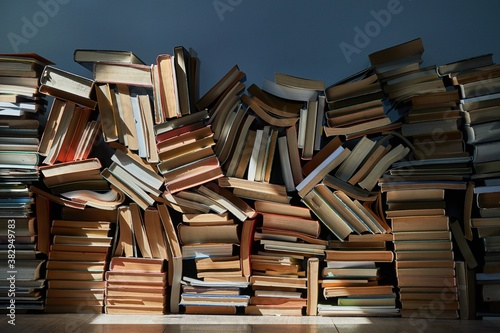Cuadros en Lienzo Pile of old books in dramatic dim light sunlight rays through window