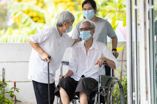 Fototapeta .Happy asian elderly woman wearing medical mask sit in wheelchair with female ca