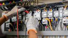 Electrician Engineer Uses A Multimeter To Test The Electrical Installation And Power Line Current In An Electrical System Control Cabinet.