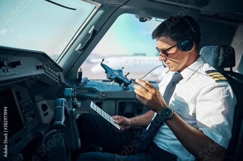 Handsome pilot preparing for departuring from airport Fotobehang