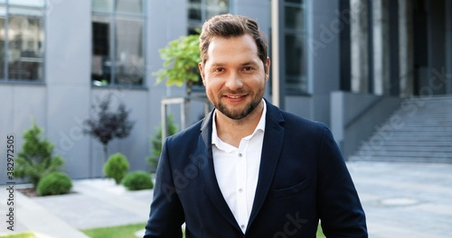 Foto Portrait of young Caucasian handsome businessman standing outdoors, turning face to camera and smiling cheerfully