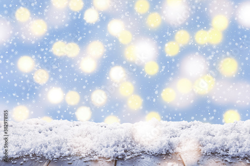 Fototapeta Closeup view of wooden table with snow against glowing Christmas lights obraz