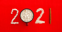 New Year's Coffee 2021. A Mug Of Coffee Or Cocoa And A Figure 2021 Composed Of Marshmallows And Coconut Shavings On A Bright Red Background.