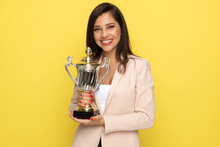 Proud Businesswoman In Pink Suit Holding Trophy