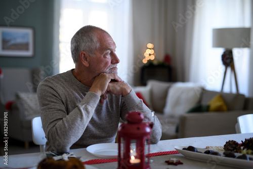 Obraz Lonely senior man sitting at the table indoors at Christmas, solitude concept. - fototapety do salonu