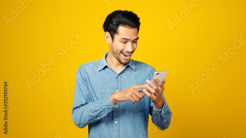 Fotografie, Obraz Asian man holding mobile phone and surprising while standing isolated on yellow