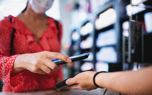 Fotografía Woman with face mask paying by smartphone indoors in shopping center, coronavirus concept