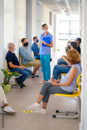 Portrait of nurse with face masks talking to patients, coronavirus, covid-19 and vaccination concept. - 382986311