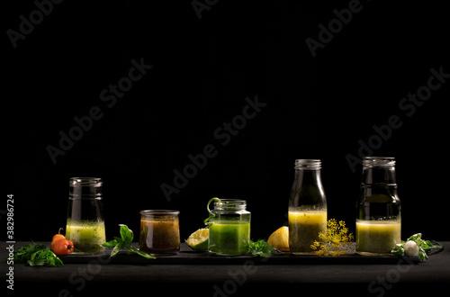 Fotografie, Obraz 5 homemade salad dressings in glass jars on a dark background.