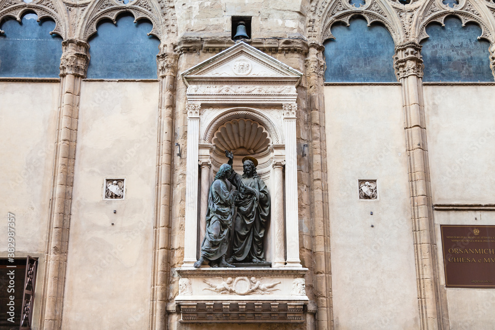 FLORENCE, ITALY - NOVEMBER 4, 2016: wall of Orsanmichele church with statue Christ and St Thomas. Church was originally built as a grain market in 1337 on the site of kitchen garden of monastery